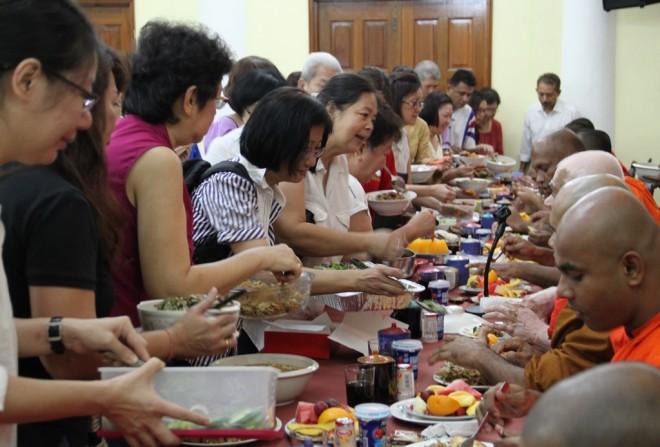 Devotees offering food to members of the Sangha.