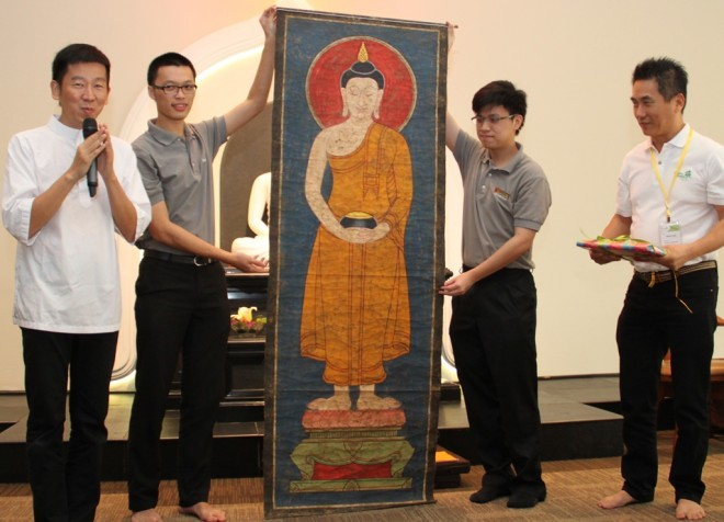 Bro. Tan presenting an old painting of the Buddha to Bro. Wilson (right).