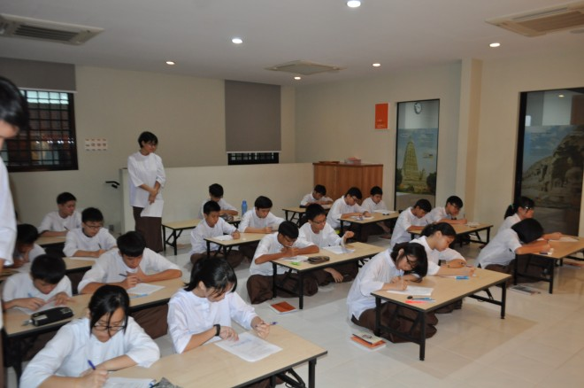 Dhamma School students at NEO Johor Bahru sitting for their year-end examination. They were tested on their basic understanding of Buddhism.
