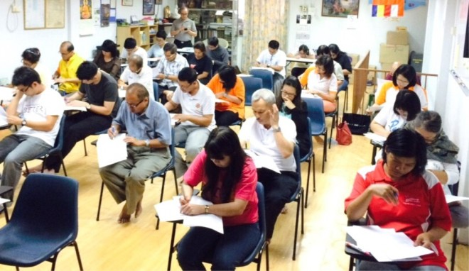Participants giving their full concentration on the examination questions.