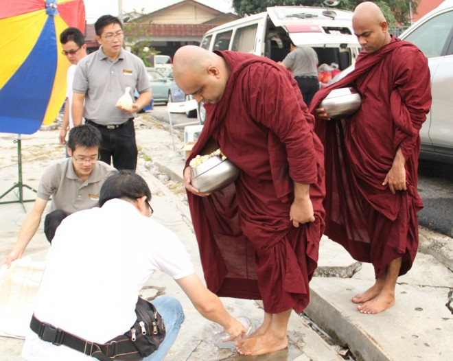 Nalandians and devotees helping the venerables to wash their feet after alms-round.