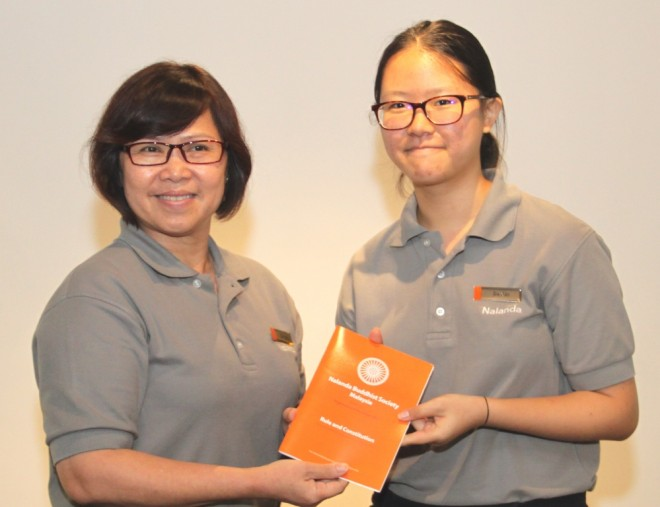 Sis. Evelyn welcomes and presents the Society's 'Rules and Constitution' booklet to Sis. Jia Xin.