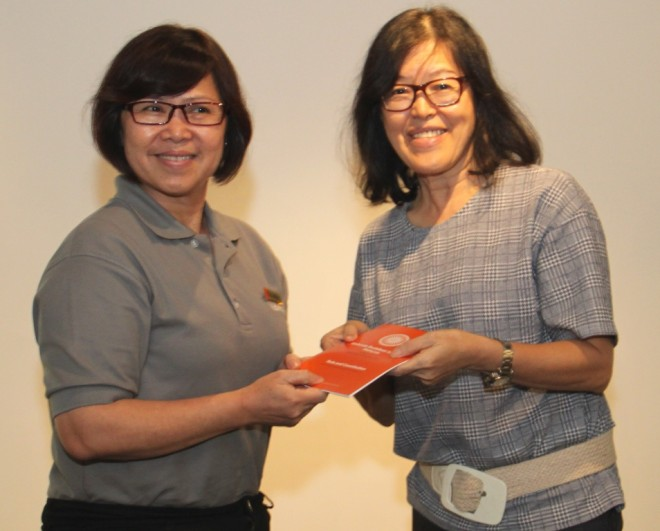 Sis. Evelyn welcomes and presents the Society's 'Rules and Constitution' booklet to Sis. Poh Peng.