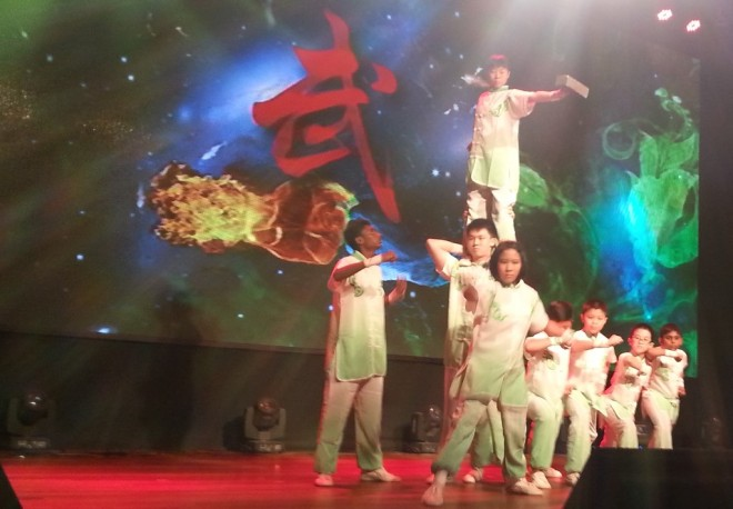 Sam Poh Tong students doing a spirited wushu performance on stage.
