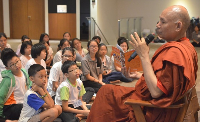 Ven. Sanghasena giving a Dhamma talk on 'Caring and Sharing' to children attending a holiday camp at Nalanda Centre.