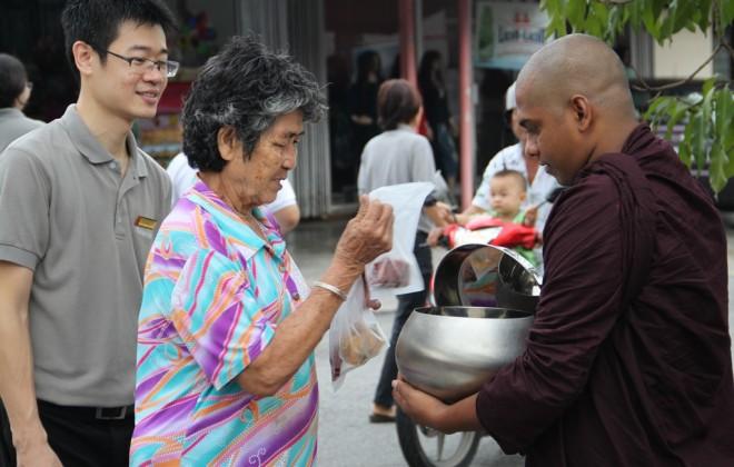Devotees offering alms to venerable bhikkhus.
