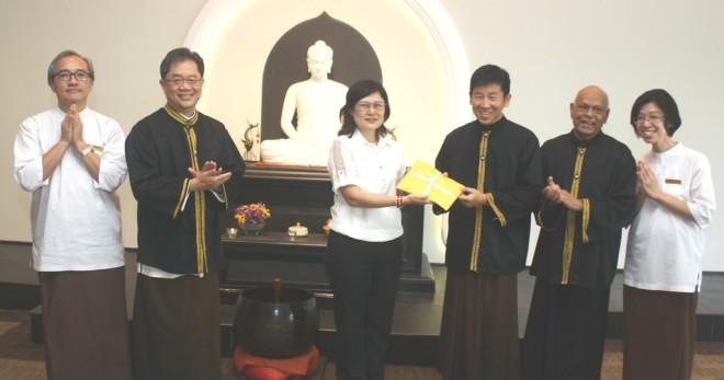 Sis. Suh Chuen receiving a prize for the Best Overall Performance in the BPS 303 Certificate in Buddhist Studies from Bro. Tan, while Achariya Vijaya, Achariya Siang Chye, Bro. Ananda and Sis. Sandy look on.