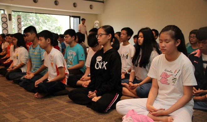 Teenagers learning to calm their minds with meditation.