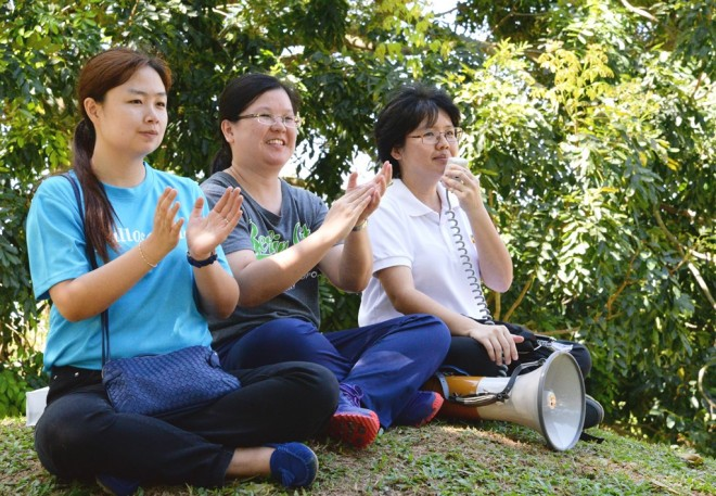 (From left) Dhamma School officers Sis. Sadhika, Sis. Hui Shien, and Sis. Sunanda clapping and cheering for the students.