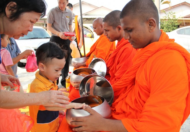 A young devotee learns to offer alms-food to the venerables.