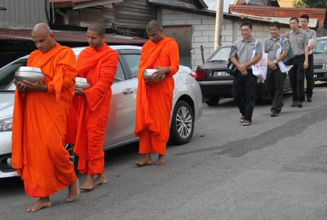 Nalanda volunteers walk reverentially behind the venerable monks on alms-round.