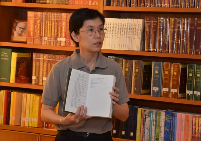 Sis. Santi showing a volume of Buddhist texts to participants.