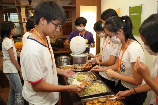 Camp participants learn the importance of teamwork and responsibility through simple chores such as serving their fellow participants during meal times.