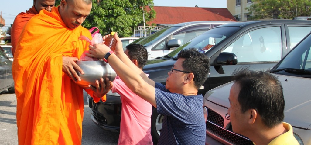 Devotees offering Dana to the venerable monks on alms-round at the Seri Kembangan market.