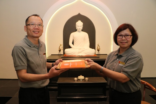 Sis. Evelyn handing a copy of Nalanda Constitution to KL Branch Chairman Bro. Ng.