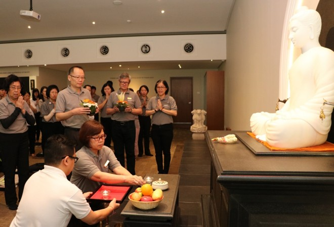 President leading the offerings to Buddha, Dhamma and Sangha.