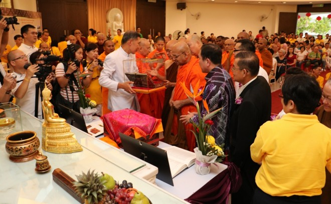 Sangha members and dignitaries viewing and worshiping the relic.