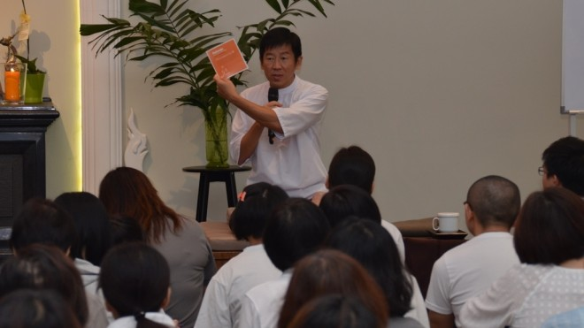 Bro. Tan reminds the congregation to keep a log of their practice in the booklet specially printed for the Gimhana retreat.