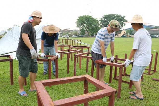 Volunteers working together harmoniously to prepare the venue for Wesak Day.
