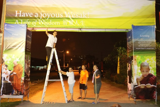 Always full of cheer, volunteers worked late into night to prepare the venue for Wesak Day.