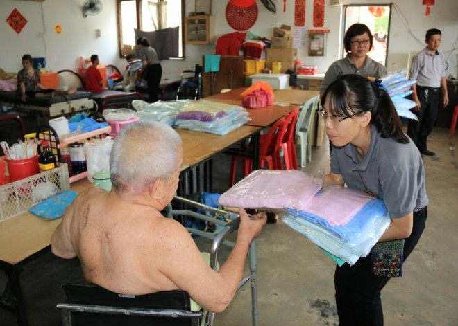 Nalandians offering towels to the senior citizens at Tong Sim.