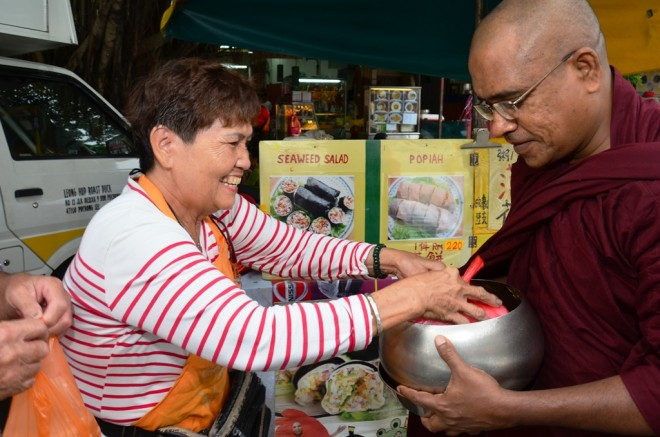 Stall owners and market-goers happily offering alms-food to the venerable monks.
