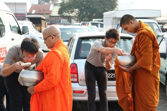 Nalanda Dhamma School students offering help as well as alms.