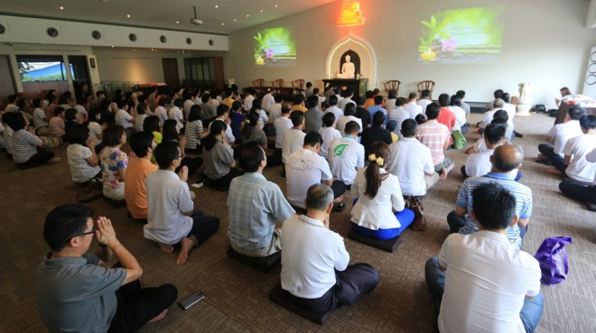 The congregation engaged in chanting and meritorious deeds on 'Sangha Day'.