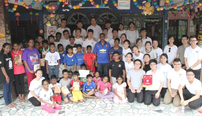 The youths with caregiver Mr. Manimaran and the children of Siddharthan Care Centre.