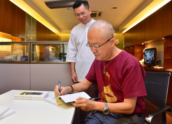 Dr. Wong autographing a few copies of his book for Nalanda Library.
