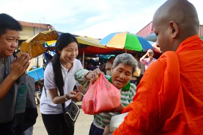 Volunteers helping an elderly lady offer food.