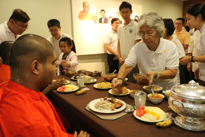 Devotees offering food to the venerable monks during lunch dāna.