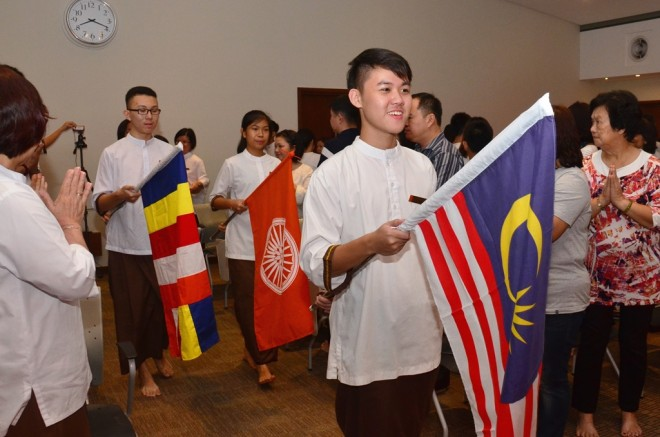 Student leaders lead the traditional procession bearing flags.