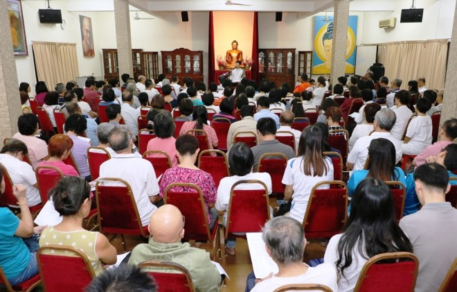 The lecture hall was filled with devotees and students.