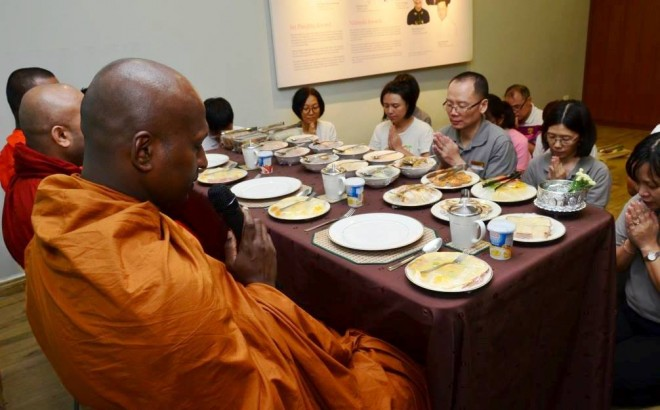 Offering the noon meal to the venerable monks after their alms-round.