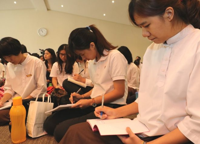 Students taking notes of the Dhamma teaching.