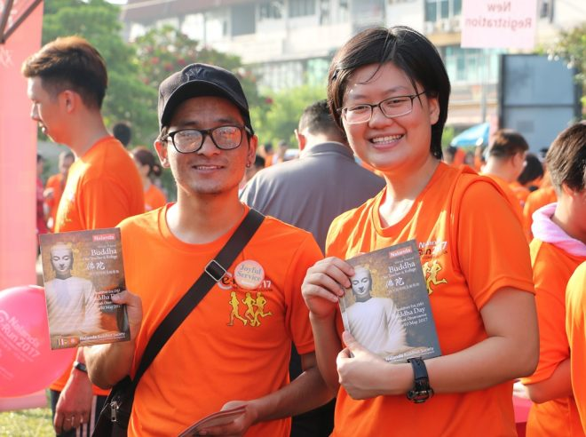 Young volunteers inviting people to Nalanda's Wesak programme.