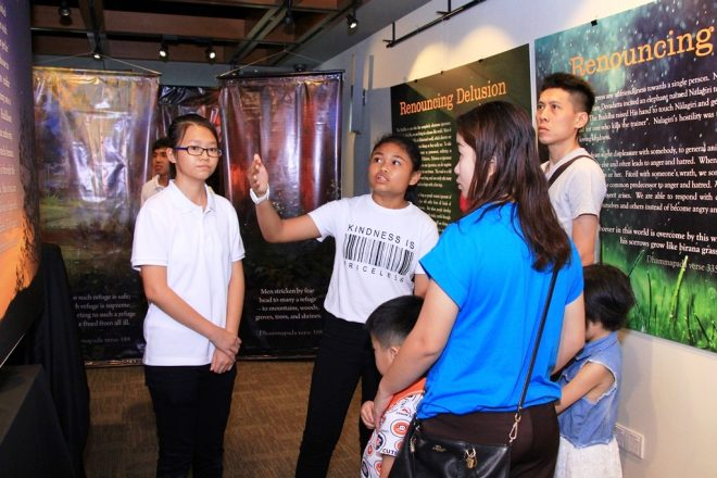 Dhamma School students showing visitors around the exhibition.