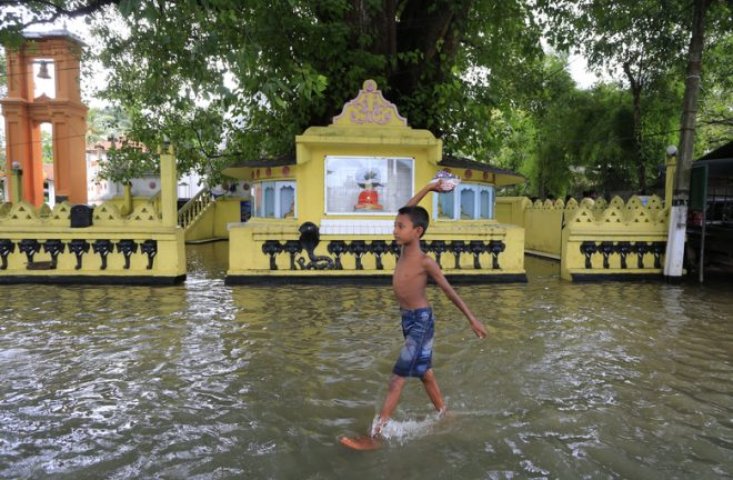 A boy with a packet of food wading through flood waters.