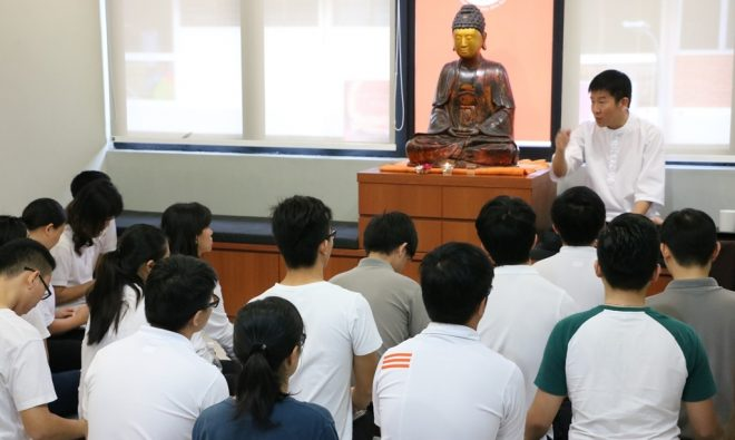 """Bro. Tan giving a teaching on the """"seven treasures"""" of Dhamma to the youths."""