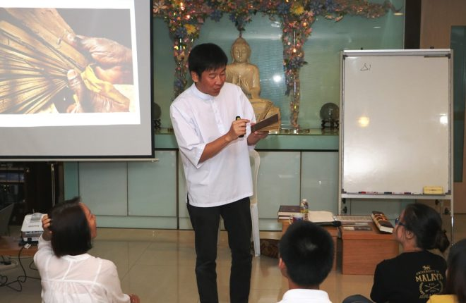 Bro. Tan showing a collection of miniature palm-leaf manuscripts.