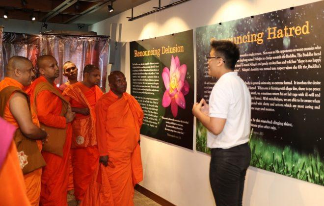 "Nalanda youth Yi Kang showing the venerables around the ""Buddha Jayanti"" Exhibition."