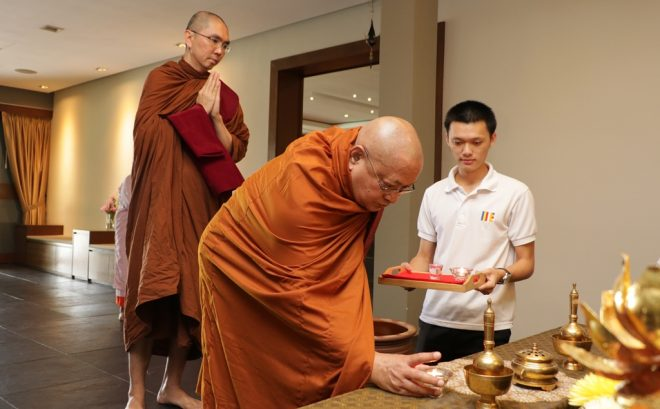 Sayadaw Nyanapurnik accompanied by Venerable Gavesi offering lamp at the Buddha-Altar.